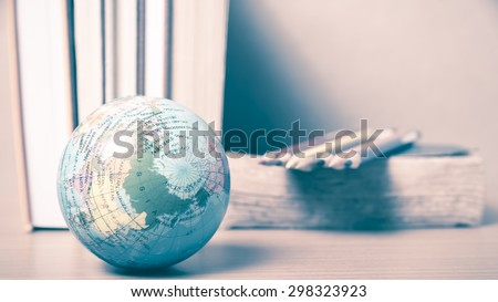 book and earth ball with color pencil on wood background vintage style - stock photo