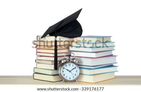 book and graduation cap with clock over on white - stock photo