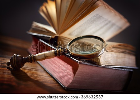 Book and magnifying glass concept for education, knowledge and searching for information - stock photo