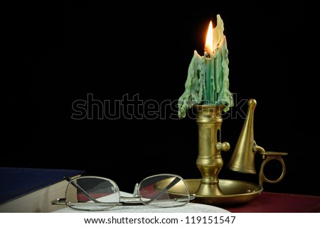 Book and spectacles against a black background lit by an antique candlestick. 36 MP image - stock photo