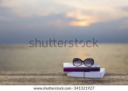 book and spectacles on wooden table on sunset sea background with selective focus, shallow depth of field. - stock photo