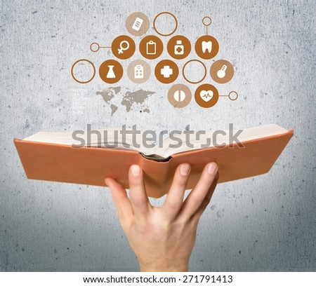 Book. Education and book concept - close up hand holding open book with magic lights - stock photo