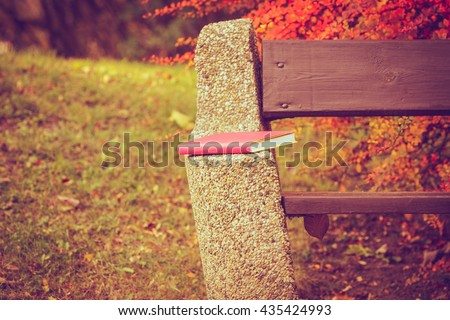 Book left on bench. Autumnal park with abandoned item. Nature outdoor vegetation relax scenery fall concept.  - stock photo