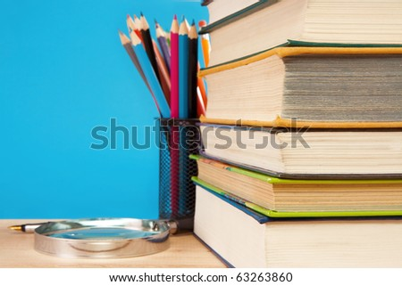 book, magnifier and holder basket with colored pencils - stock photo