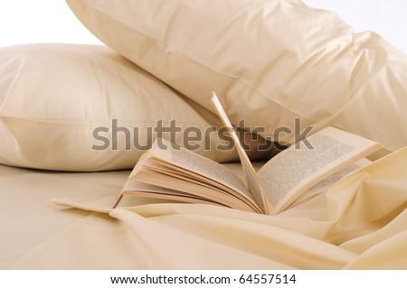 Book on messy bed. - stock photo