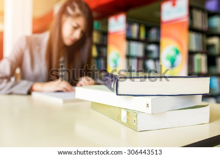 Book on table on blur background of Student with open book reading it,In college library - stock photo