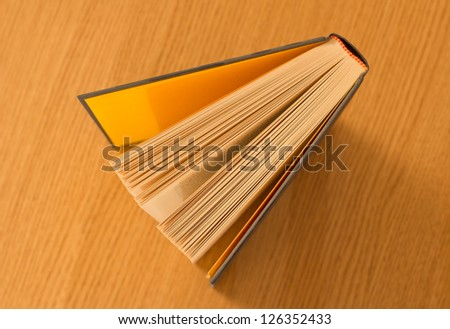 Book on wooden table viewed above - stock photo