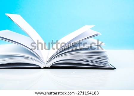 Book. Open book on table, blue background - stock photo