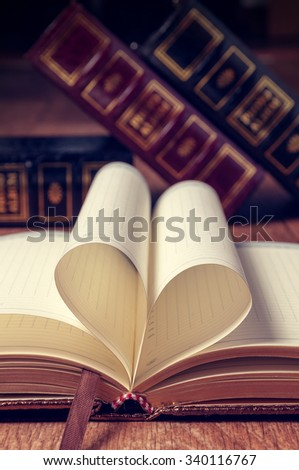 Book page in heart shape with library background. - stock photo