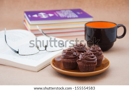 Book reading pause with mini chocolate cupcakes  - stock photo