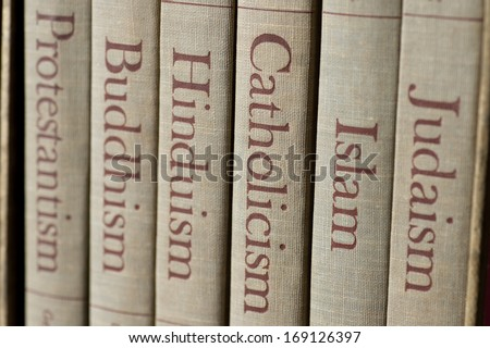 Book spines listing major world religions - Judaism, Islam, Catholicism, Hinduism, Buddhism and Protestantism. The focus is on the word, Catholicism. - stock photo