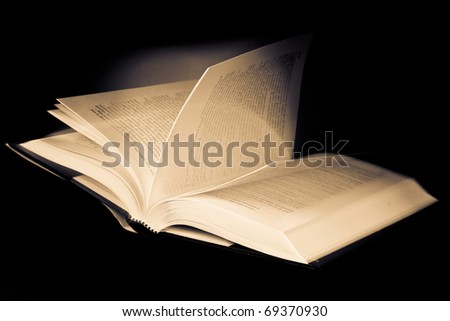 book with browsing pages against black background - stock photo