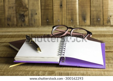 book with glasses and pen on the wooden background. - stock photo