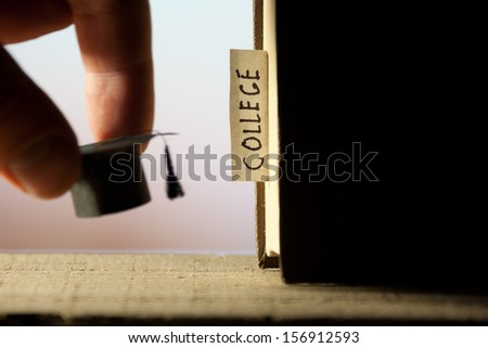 """Book with label """"college"""" and graduation cap.  - stock photo"""