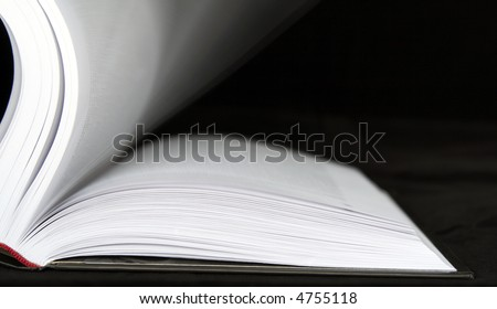 Book with moving sheets on a black background - stock photo