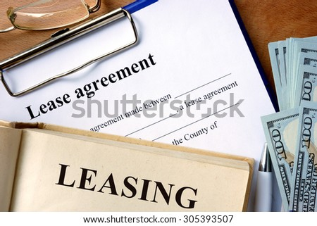 Book with word leasing,  lease agreement form and money. - stock photo