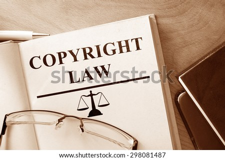 Book with words Copyright Law and glasses. - stock photo