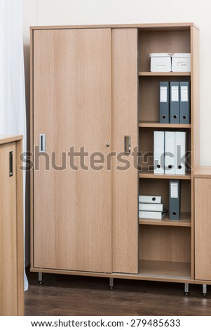 bookcase with folders and boxes in office - stock photo