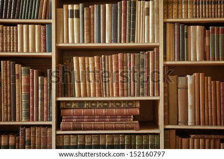 bookcase with many old books in a  library - stock photo