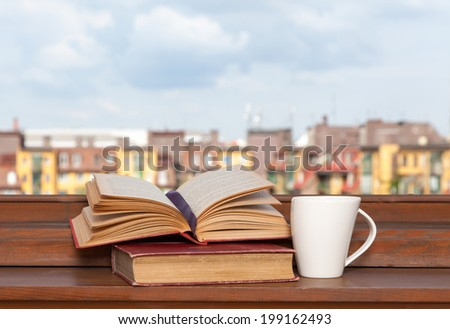 Books and a coffee cup on a windowsill - stock photo