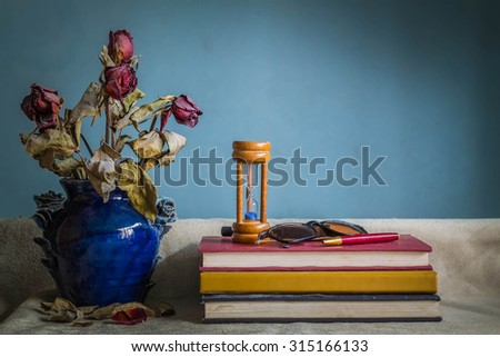 Books and a vase of dried flowers on the table. - stock photo
