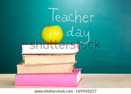 Books and apple on blackboard background with inscription Teacher Day - stock photo