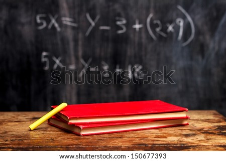 Books and chalk by blackboard with equation - stock photo