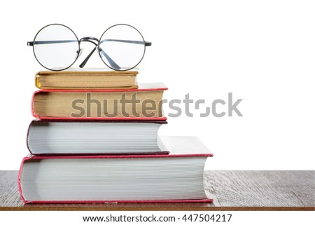 Books and eyeglasses on a table with isolated background - stock photo