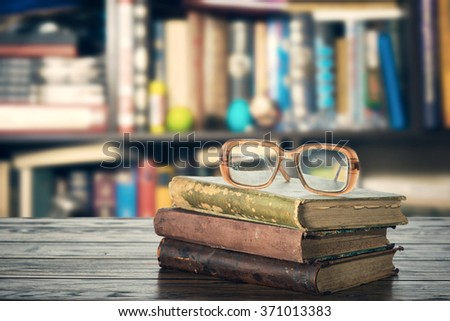 Books and eyeglasses on the shelf - stock photo