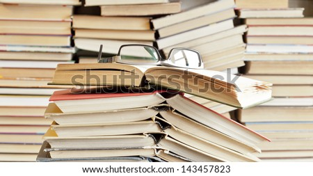books and glasses on table front of a full bookshelf copy Space for inscription - stock photo