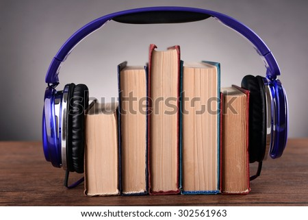 Books and headphones as audio books concept on wooden table on grey background - stock photo