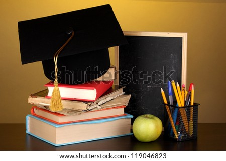 Books and magister cap against school board on wooden table on yellow background - stock photo