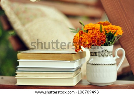 Books and marigolds in a vase stock image - stock photo