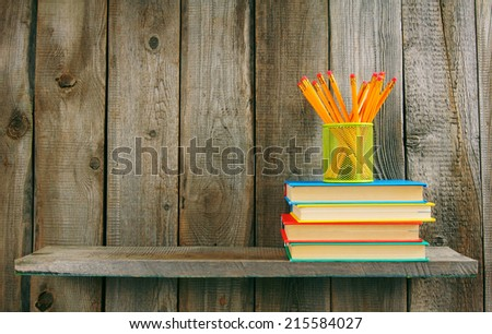 Books and pencils on a wooden shelf. On a wooden background. - stock photo