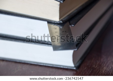 Books and ruler. Metal twenty centimeters ruler.  - stock photo