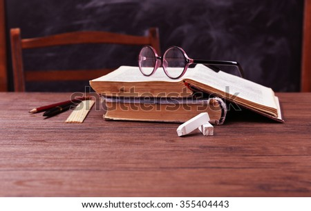 Books and school accessories on wooden table - stock photo
