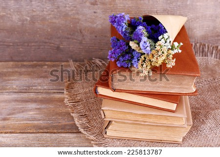 Books and wildflowers on napkin on wooden table on wooden wall background - stock photo