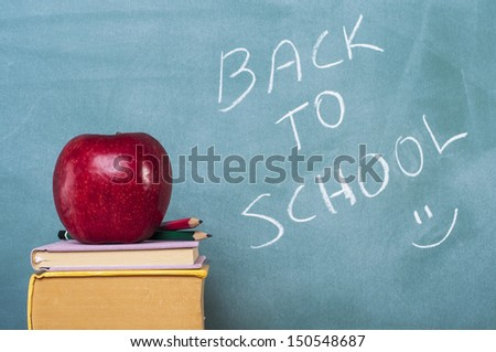 books apple and pencil in front of green chalkboard - stock photo