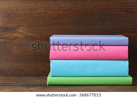 books in color cover folded stack on the wooden table - stock photo