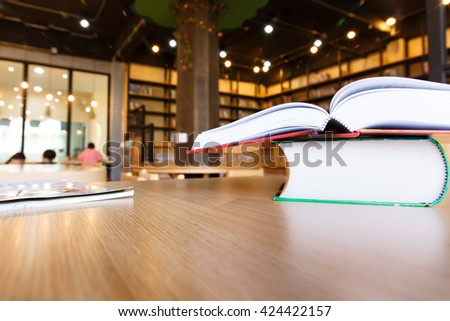 Books in public library with blurred student and book shelves. - stock photo