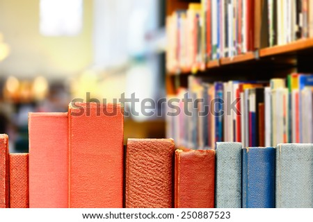 Books in row, library shelves in background - stock photo
