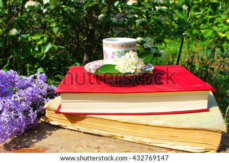 Books, lilacs and Cup of tea in the garden - stock photo