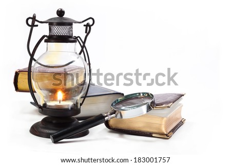 Books, magnifying glass and lamp with burning candle on white background - stock photo