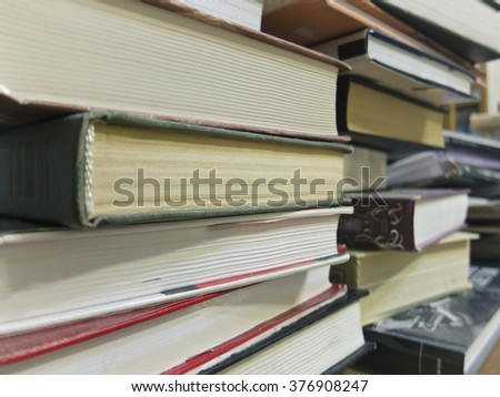 Books of different sizes and colors are a big stack in a pile on each other - stock photo