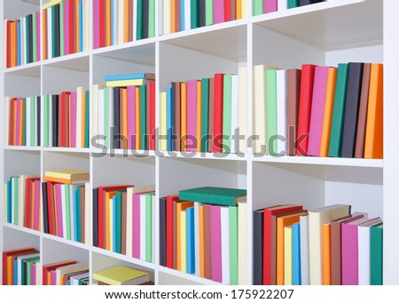 Books on a white shelf, stack of colorful books in Library - stock photo