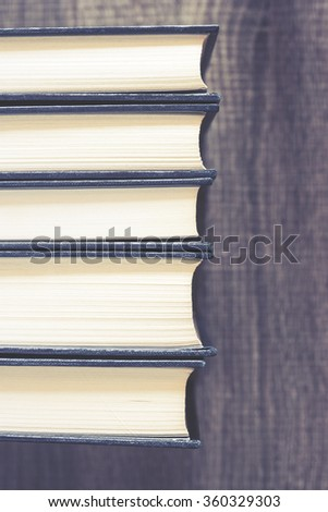 Books on a wooden desk. Selective focus image cross processed for vintage look - stock photo