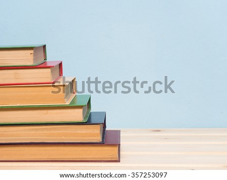 Books on a wooden shelf on a blue background - stock photo