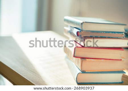 Books on the table in front of sunlight. Shallow depth of field. - stock photo