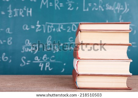 Books on wooden table on blackboard background - stock photo
