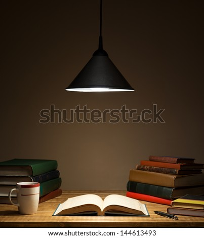 Books on wooden table under lamp light - stock photo
